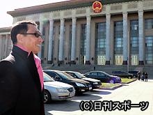 上映会会場となった北京・人民大会堂(後方)周辺を見渡し、笑顔の中井貴一
