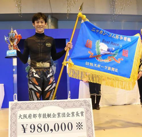 優勝旗、優勝カップを手に笑顔を浮かべる古結宏