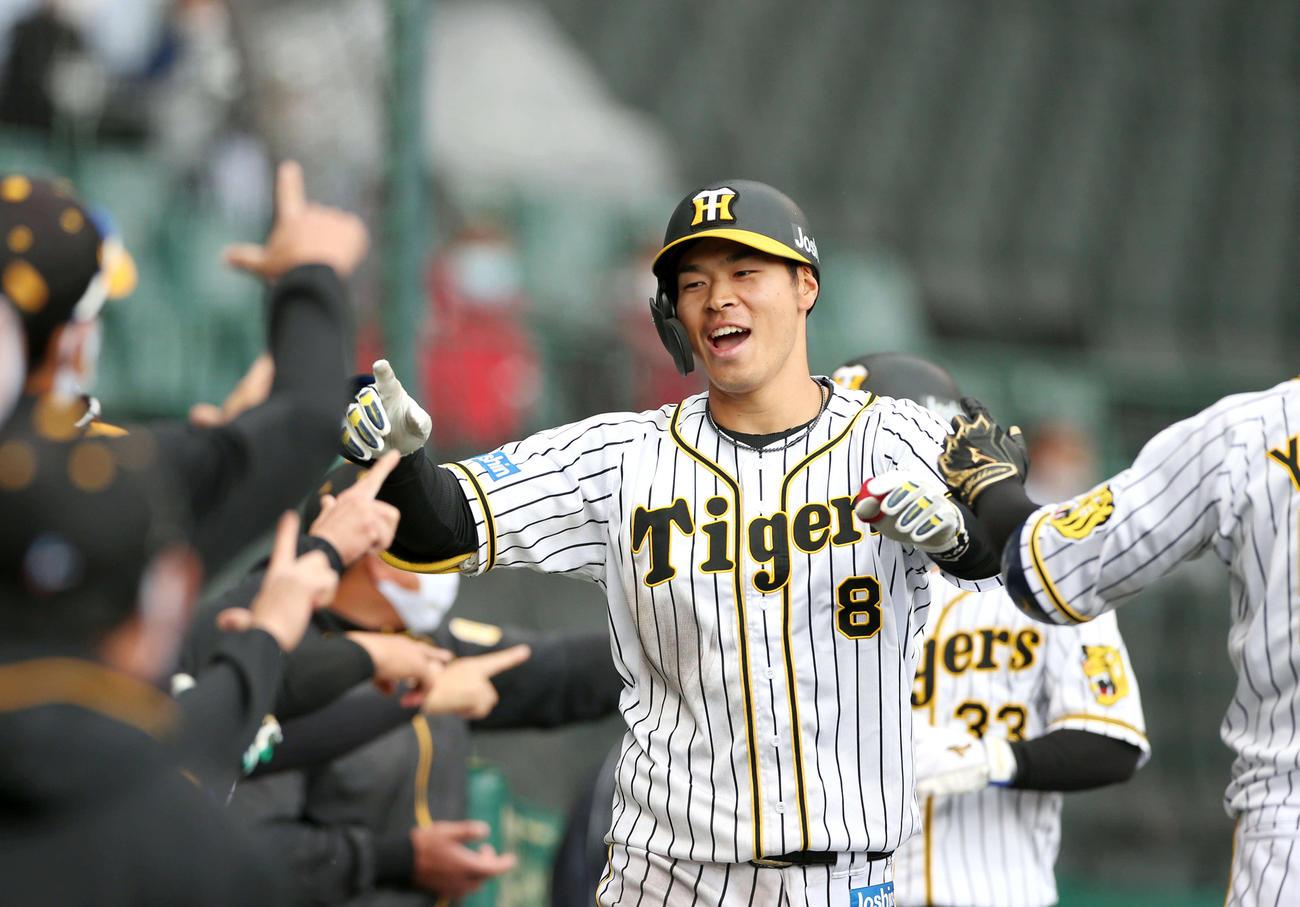 5回裏阪神無死満塁、佐藤輝は右越え満塁本塁打を放ちナインの出迎えに笑顔を見せる(撮影・上山淳一)