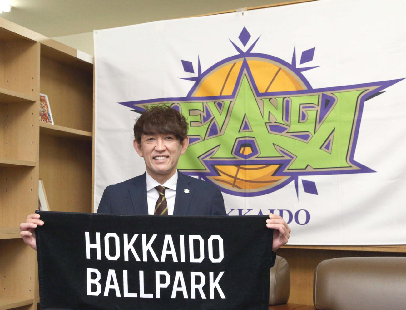 日本ハムのボールパークが印字されたタオルを持ち撮影に応じるレバンガ北海道折茂社長(撮影・佐藤翔太)