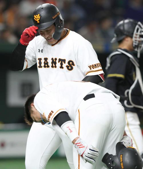 4月4日、中越え2点本塁打の岡本(奥)は頭を深々と下げて迎える一塁走者坂本勇に恐縮する(撮影・松本俊)