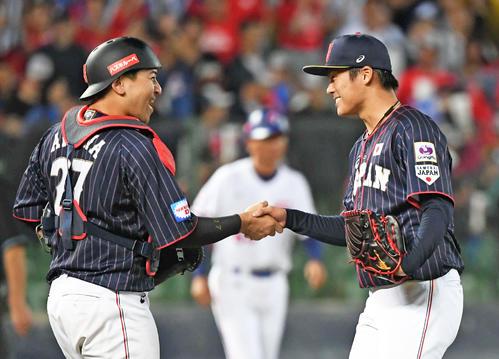 台湾を下した山本由伸(右)と会沢翼は笑顔で握手する(2019年11月7日撮影)
