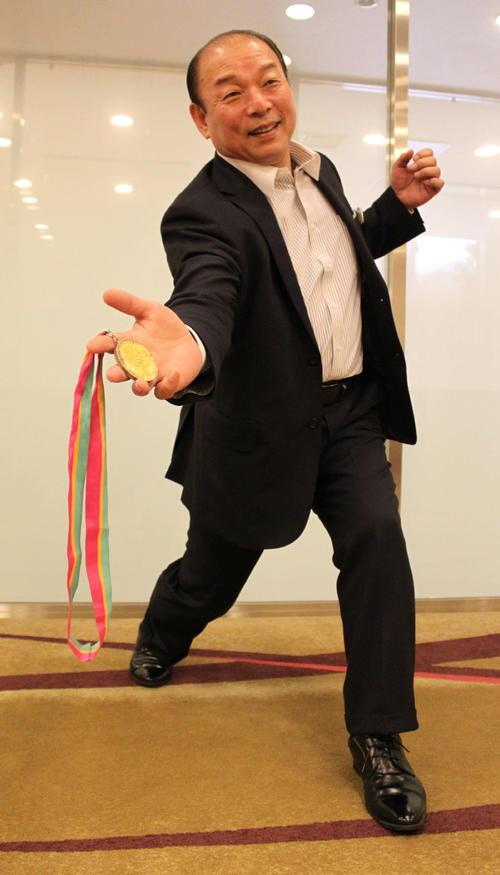 ロス五輪の金メダルを手に下手投げのフォームを披露する吉田幸夫さん