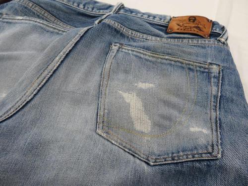 右の尻ポケットと左ももが破れた「桃太郎ジーンズ」