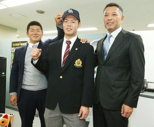 14年11月、父の近藤真市コーチ(右)の横でガッツポーズする中日育成4位の近藤。左は清水スカウト