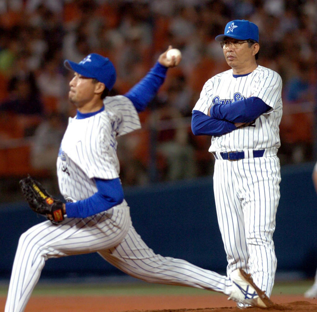 04年6月、巨人戦で投手交代の際に投球練習を見つめる横浜の小谷正勝投手コーチ(右)