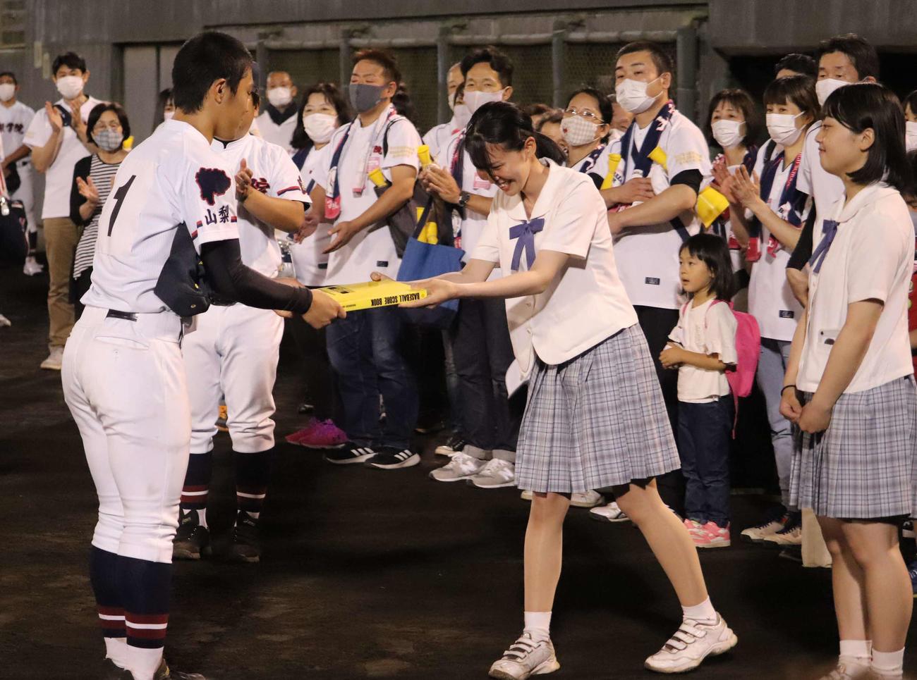 河瀬貴洋投手(左)は、マネジャーからスコアブックを受け取る(撮影・湯本勝大)