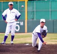 菅原コーチ(左)の指導を受けながら、ブルペンで投球する金足農・吉田