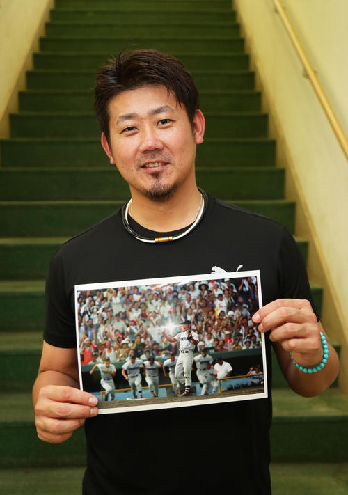 第80回夏の甲子園で優勝を決めた瞬間の写真を手に笑顔の中日松坂(撮影・足立雅史)