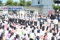 学校の駐車場で開催された準優勝報告会で、拍手を受けながら入場する金足農ナイン(撮影・神稔典)
