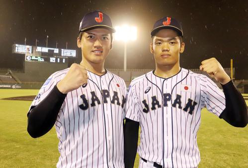 香港対日本 初戦を勝利し、投打で活躍した日本の野尻(左)と根尾はガッツポーズで写真に納まる(撮影・垰建太)