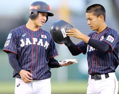 日本対スリランカ 1回表の攻撃を終え、根来(右)からヘルメットを受け取る一塁コーチの吉田(撮影・垰建太)