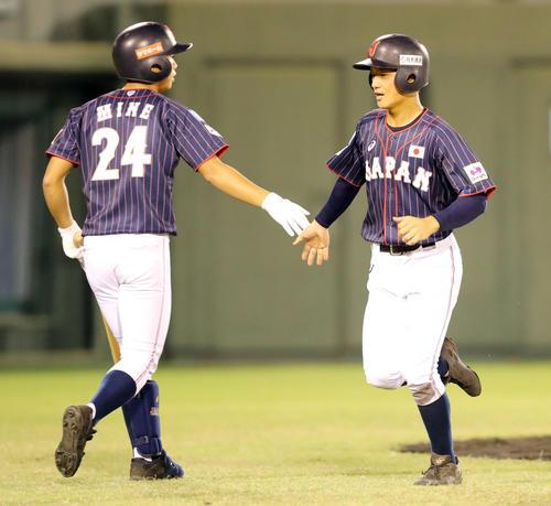 日本対スリランカ 5回表日本2死三塁、藤原の適時二塁打で生還した奈良間(右)は峯とタッチを交わす(撮影・垰建太)
