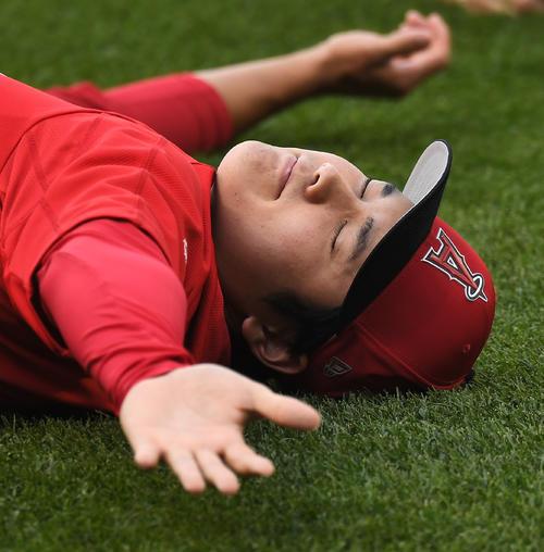 18年7月、マリナーズ戦の試合前の練習で、芝の上に寝ころび気持ちよさそうにストレッチをするエンゼル大谷