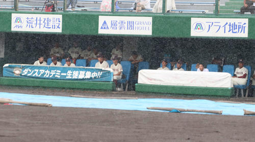 旭川大高-クラーク戦は雨のため開始予定時刻の13時に試合が開始されず、一塁側ベンチでグラウンドを見つめる旭川大高ナイン(撮影・浅水友輝)