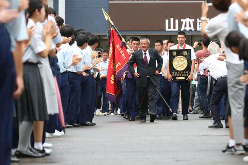 決勝戦から一夜明け学校に到着した履正社ナインは駆けつけた生徒たちの花道で祝福を受ける(撮影・上山淳一)