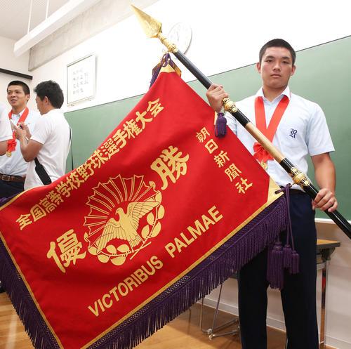 決勝戦から一夜明け学校で優勝旗を手にする野口主将(撮影・上山淳一)