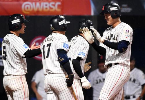 日本対パナマ 5回裏日本2死一、三塁、左越え3点本塁打を放ちナインとタッチを交わす石川(右)(撮影・横山健太)