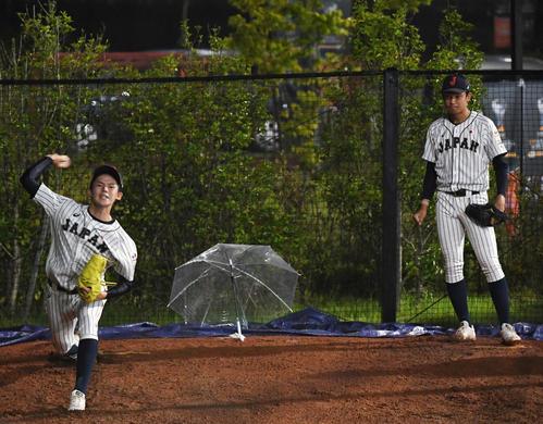 日本対パナマ 試合中、ブルペンで投球練習する佐々木(左)と奥川(撮影・横山健太)