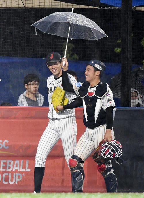 日本対パナマ 6回裏途中、雨で試合が中断し、ブルペンから傘を差しベンチへ戻る佐々木(左)と山瀬(撮影・横山健太)