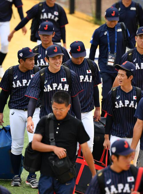 日本対韓国 笑顔で球場入りする佐々木(中央)(撮影・横山健太)