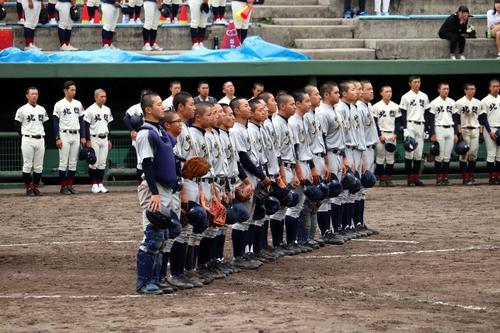 校歌を歌う岩内の選手と、敗退しベンチ前で整列する北照の選手たち(提供)