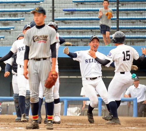 サヨナラ勝ちで初優勝を決め、歓喜する藤枝明誠の選手の手前で、ぼうぜんと立ち尽くす加藤学園のエース肥沼(左)