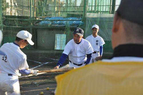 履正社の岡田龍生監督(中央)はほうきを使って打撃指導する