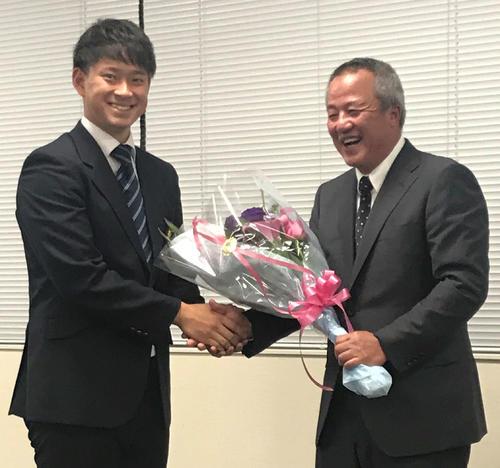 講演後、ヤクルト2位の吉田(左)から花束を受け取る履正社・岡田監督(撮影・古川真弥)