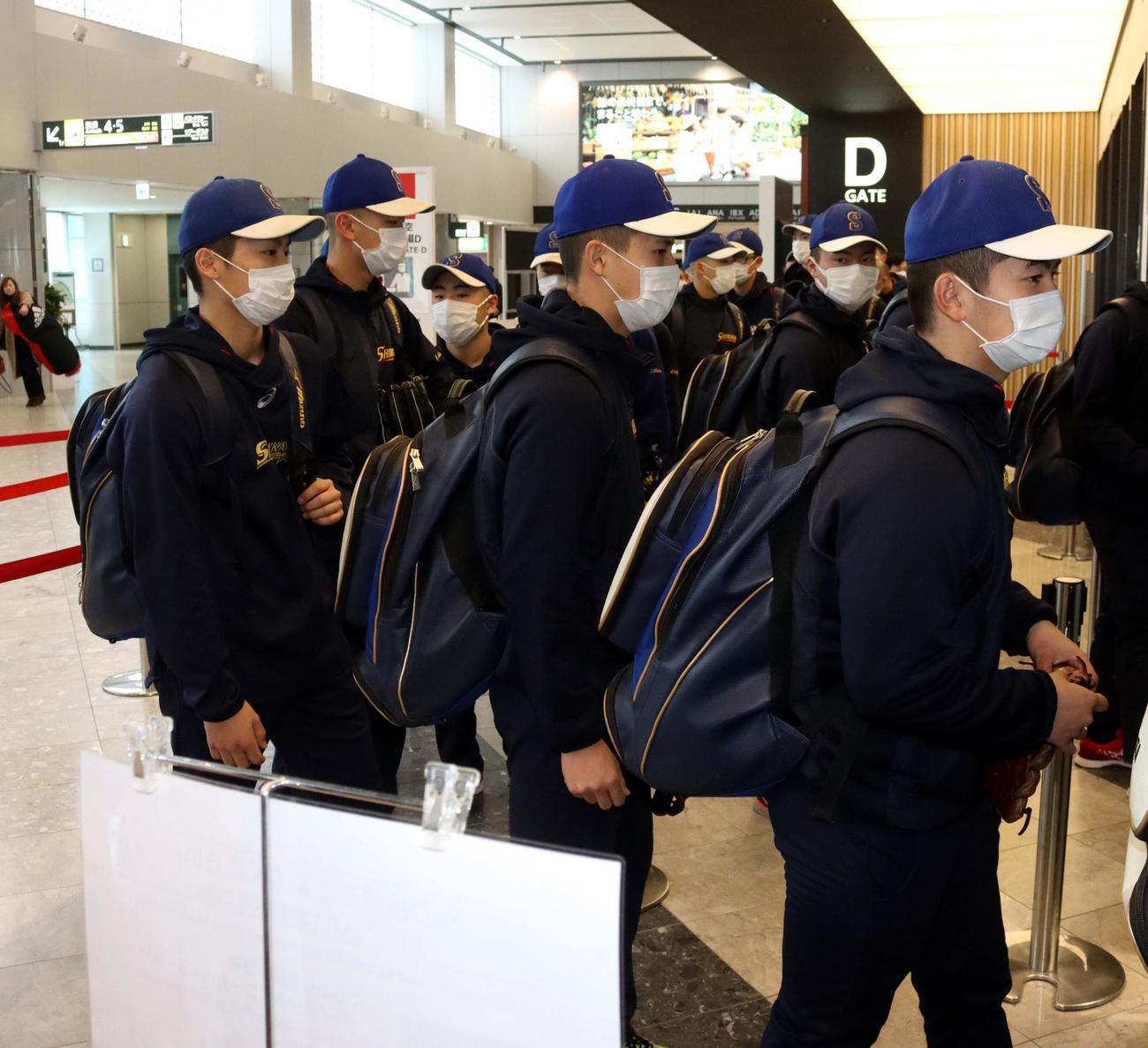 マスクを着用し新千歳空港の保安検査場前に並ぶ白樺学園の選手たち(撮影・永野高輔)
