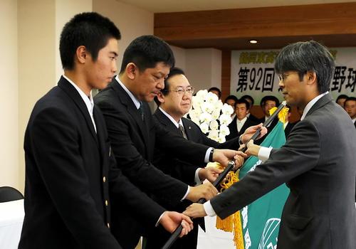 選抜旗を受け取る鶴岡東の、左から鈴木主将、佐藤監督、斎藤校長