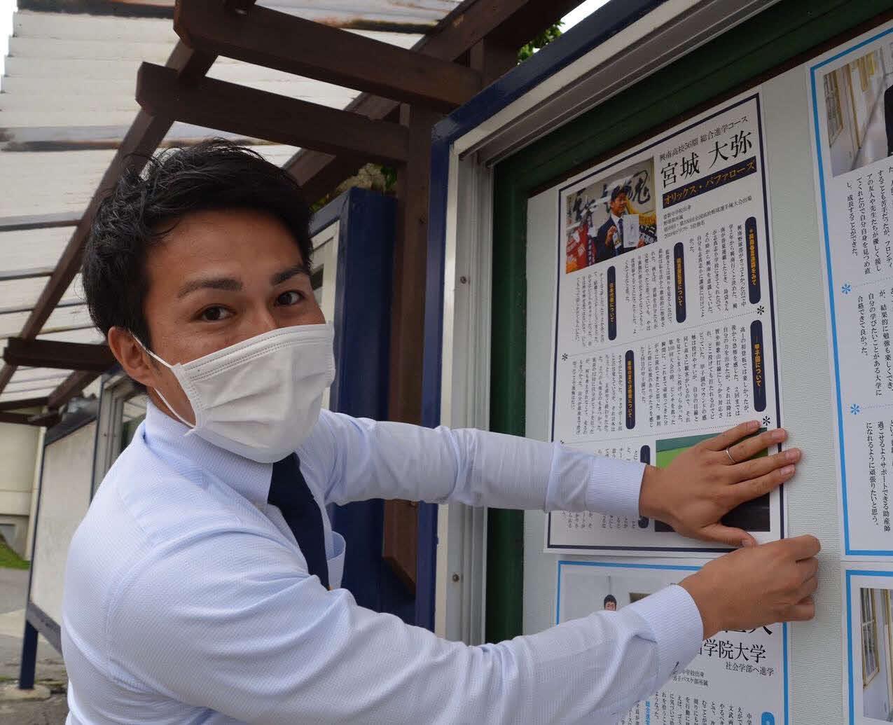 興南の事務職員、広報室に配属となった元ソフトバンク島袋洋奨さんは、学校内の掲示板に卒業生の進路が書かれた紙を張り出す(本人提供)