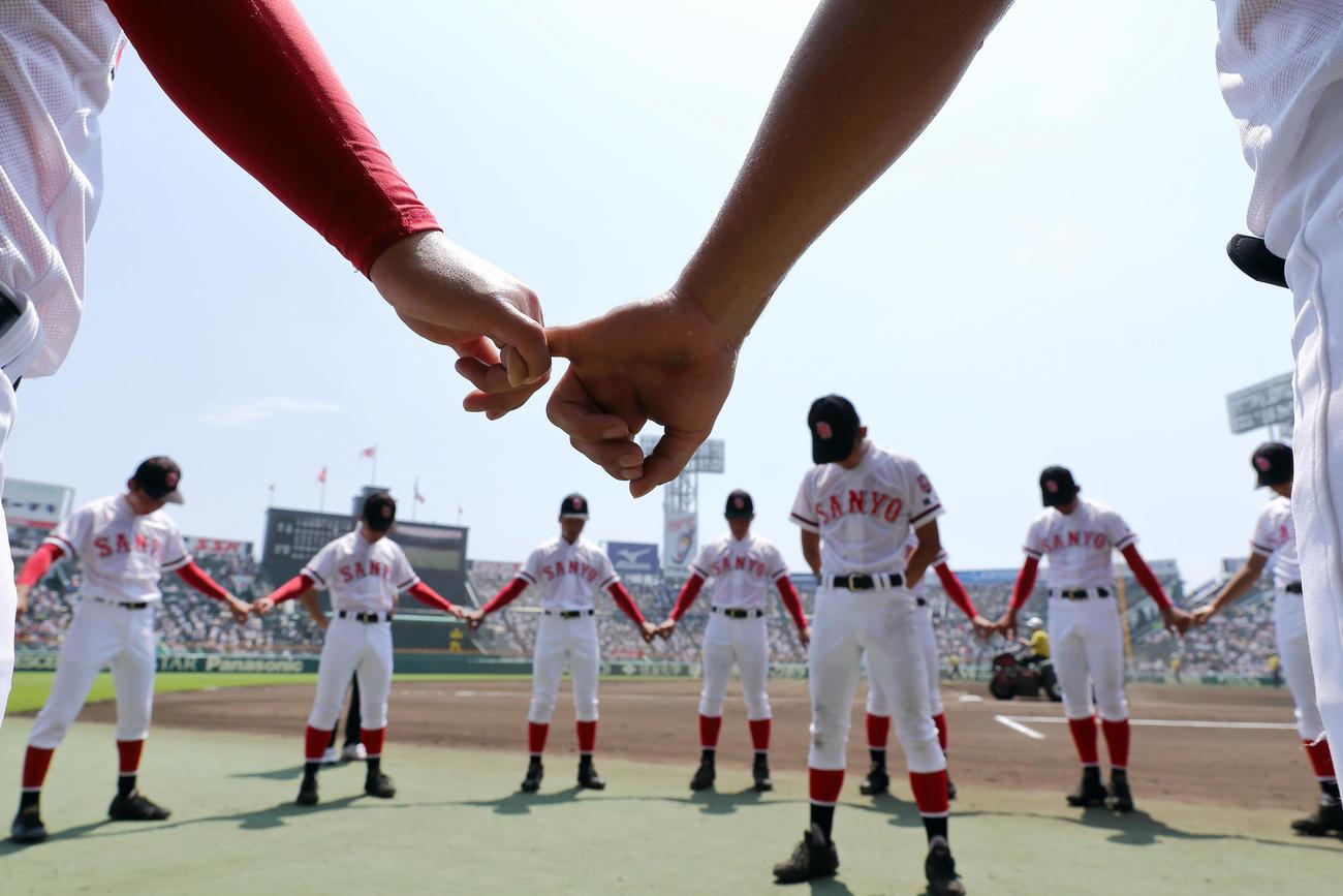 17年8月10日、聖光学院対おかやま山陽 試合前、目を閉じ手を取り合い気持ちを落ち着かせるおかやま山陽ナイン