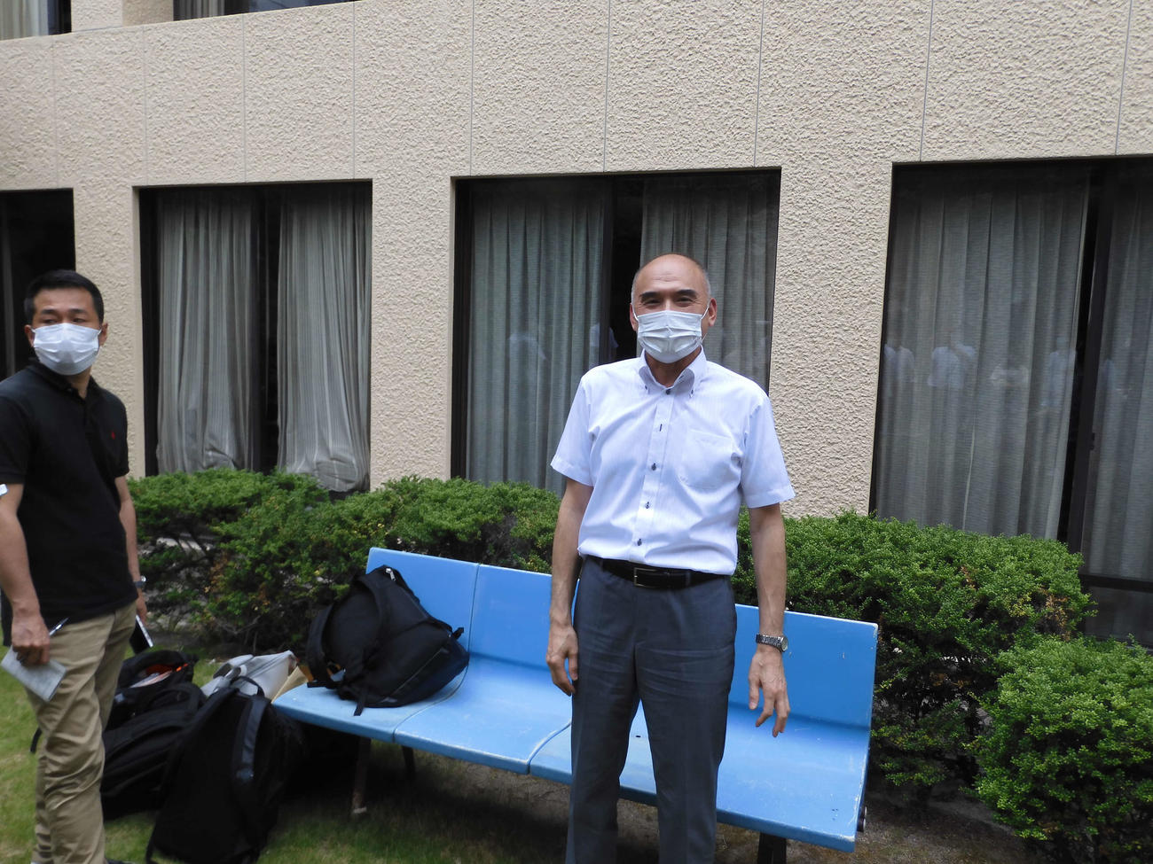 日本高野連の小倉好正事務局長(右)は、事務局の中庭で報道陣に対応する