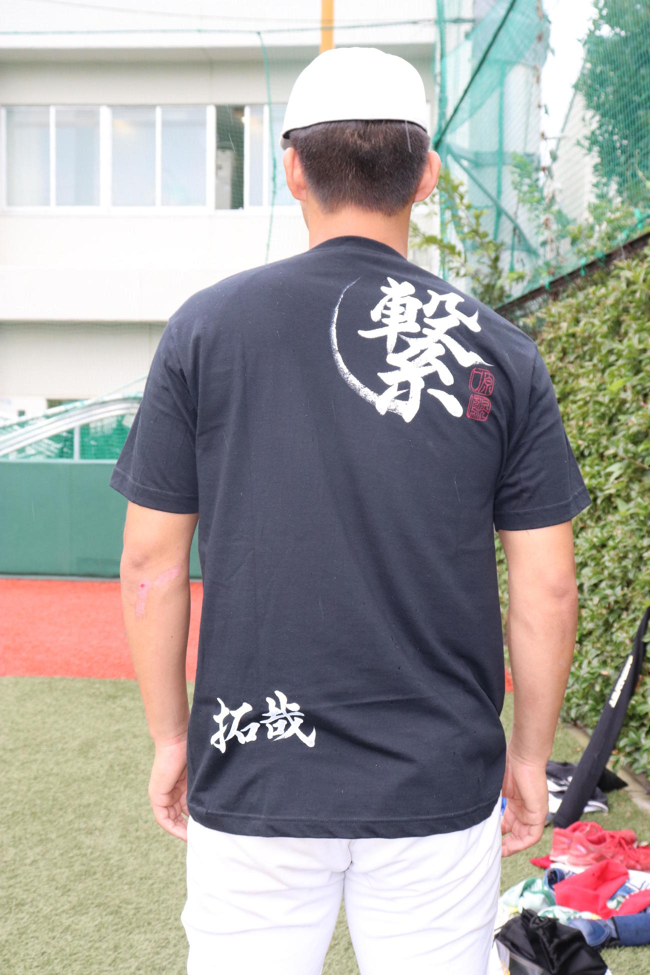 OBである阪神原口から贈られたTシャツを着る帝京・加田。裏には「繋」の文字と、各選手の名前が記されている(撮影・古川真弥)