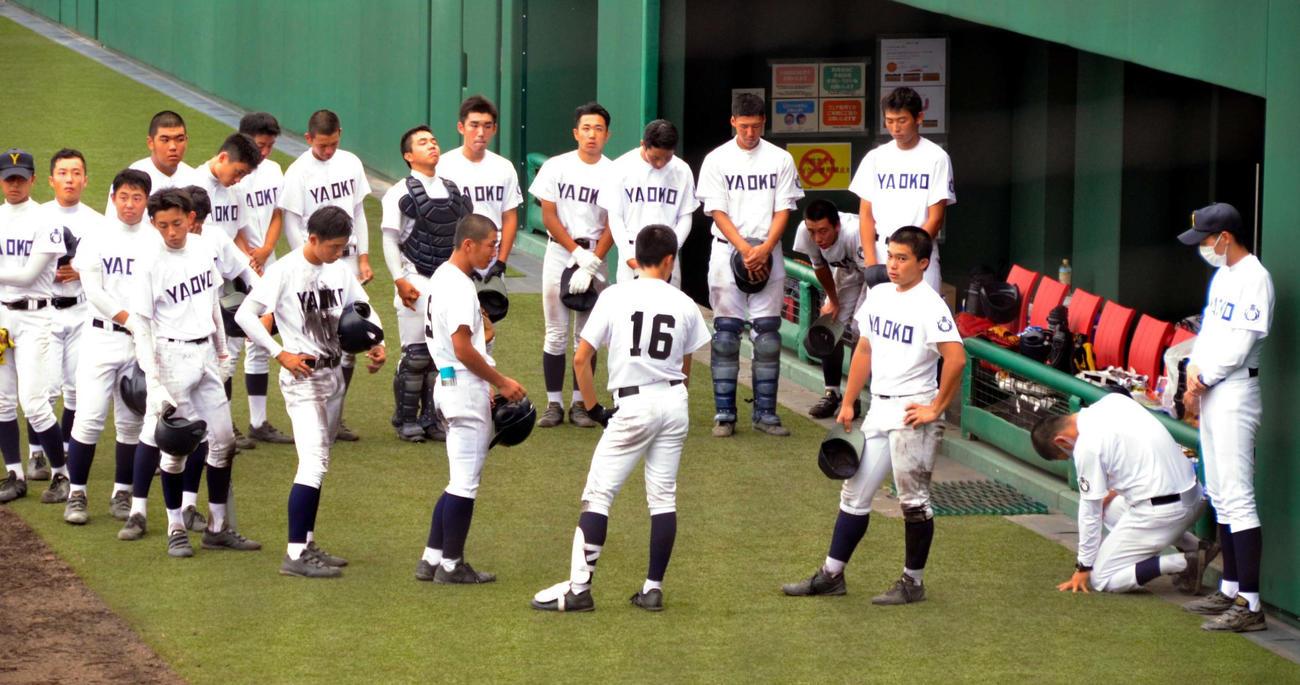 グラウンドにひざをつき、「ほんま、ごめん」と選手らに謝る八尾の長田監督(右から2人目)(朝日新聞社提供)