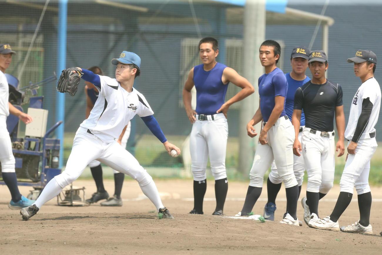 決勝の前日練習で後輩相手に打撃投手を務める聖光学院OBの須藤さん(左)(撮影・野上伸悟)