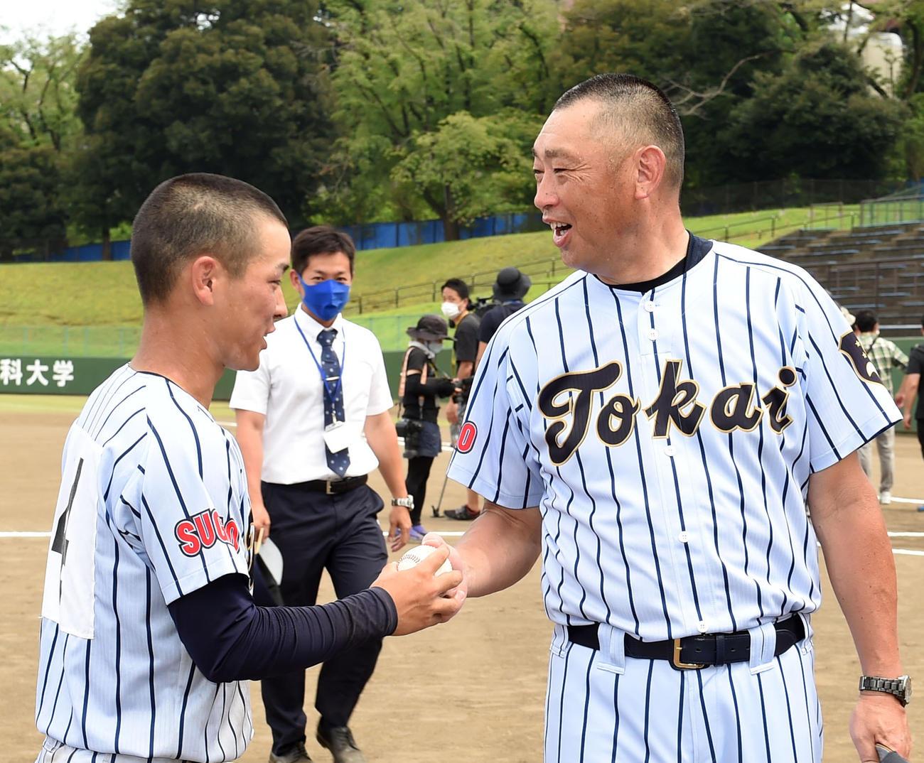 表彰式後、東海大菅生・玉置(左)からウイニングボールを受け取る若林監督(撮影・横山健太)