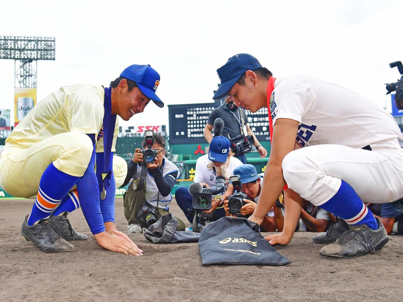 昨年の夏の甲子園で、閉会式を終え最後にマウンドで土を集める星稜・奥川恭伸(左)と履正社・清水大成(2019年8月22日撮影)