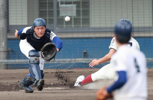 2回表大阪桐蔭1死一塁、左中間へ先制適時二塁打を放つ吉安、履正社の関本捕手(撮影・清水貴仁)