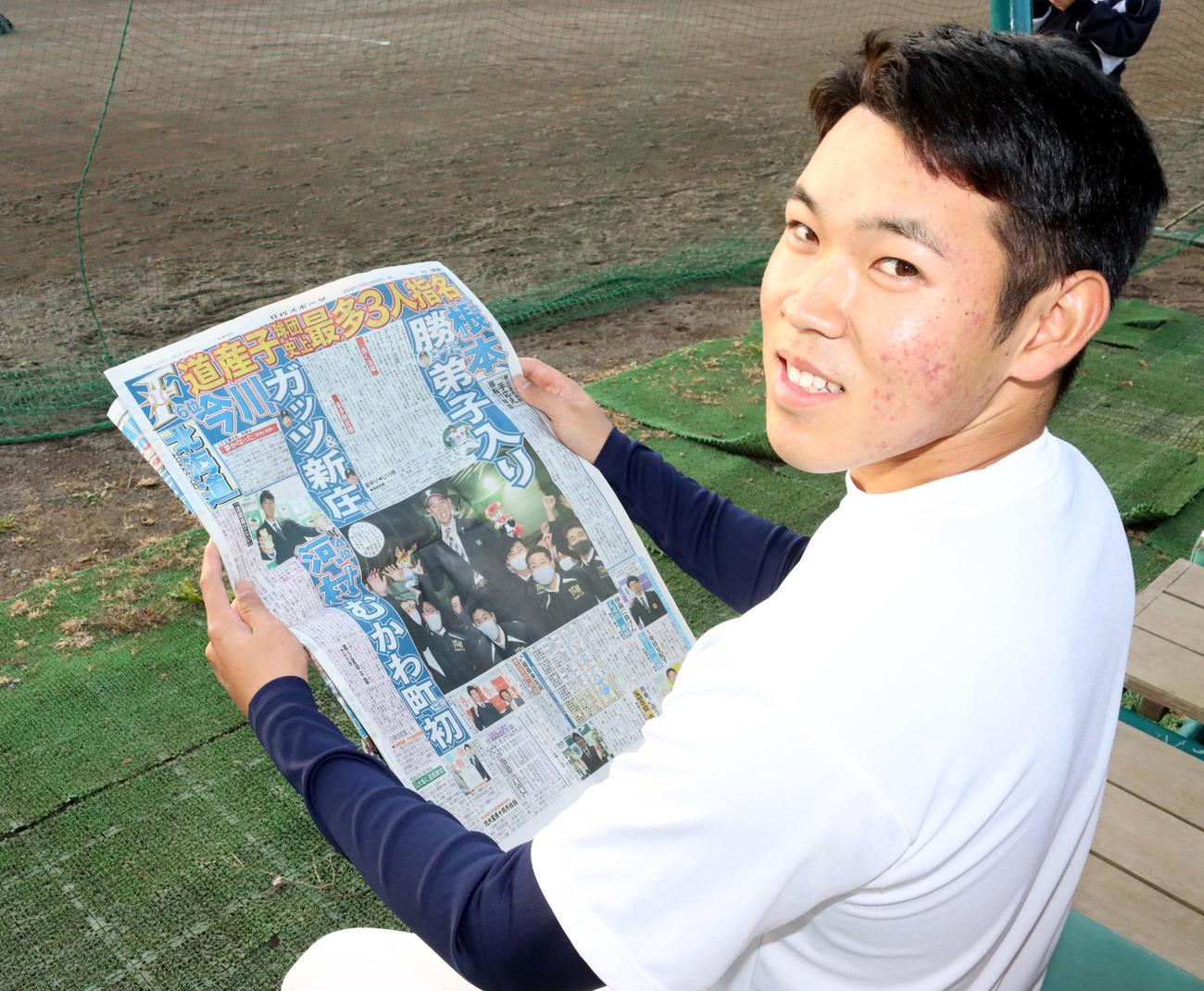 根本はドラフト結果が報じられた日刊スポーツ北海道版を手に笑顔(撮影・永野高輔)