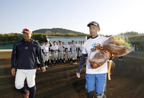 智弁和歌山の指導を終え、花束を手に引き揚げるイチローさん。左は中谷仁監督(代表撮影)