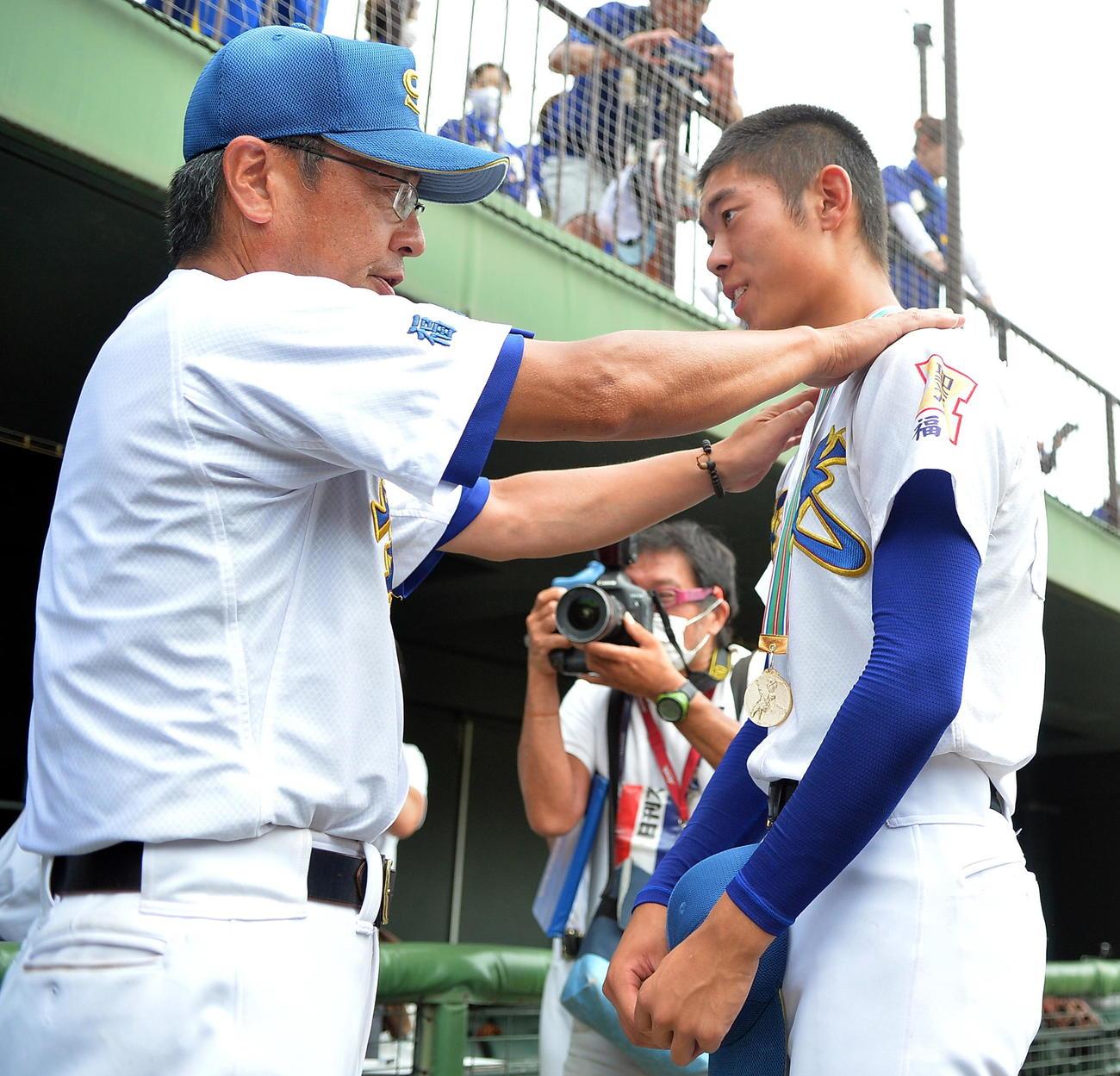 昨年8月7日、福島独自大会で優勝して斎藤監督(左)から金メダルをかけられ笑顔を見せる聖光学院・舘池