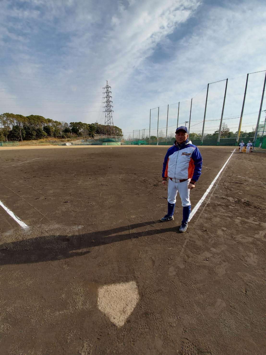 被災当時、本塁から中堅方向に亀裂が走ったグラウンドに立つ神戸国際大付・青木監督(撮影・酒井俊作)