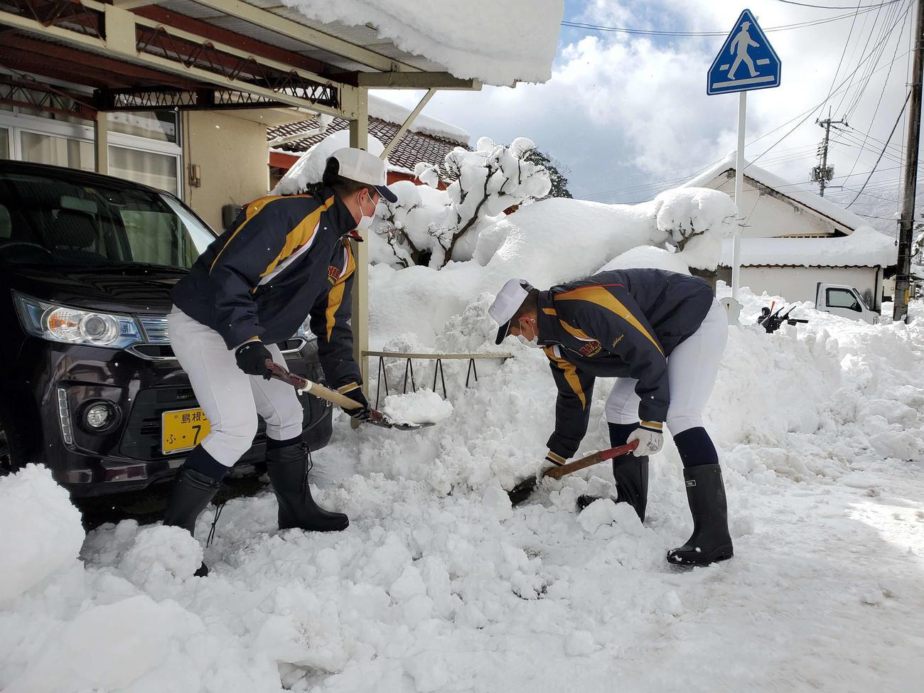 ユニホーム姿で街中に降り積もった雪を除雪する矢上ナイン(チーム提供)