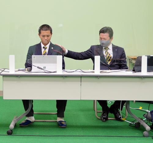 選手宣誓の当たりくじを引き当て、笑顔を見せる須江監督(右)と少し引きつった表情の島貫(撮影・佐藤究)