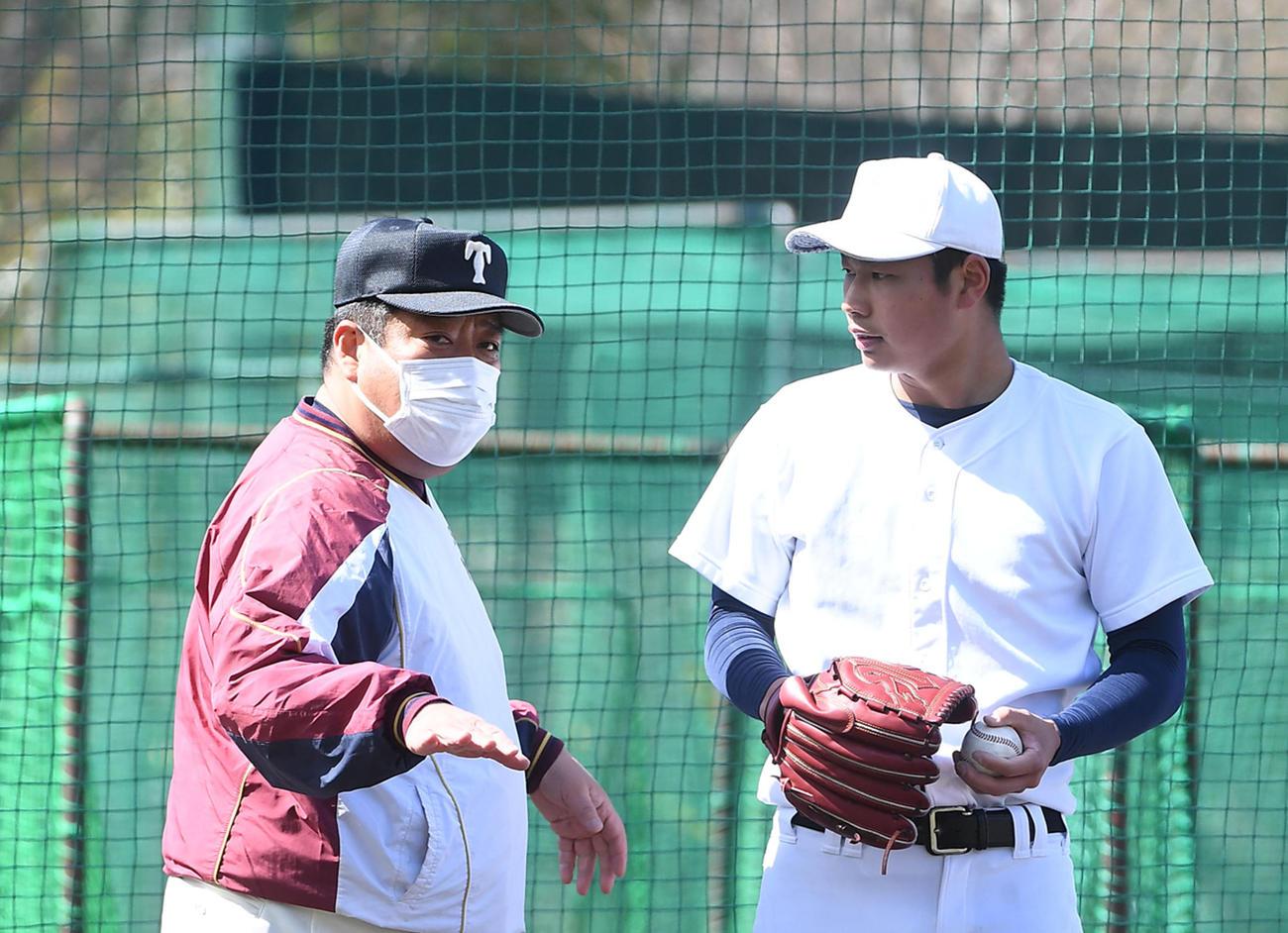 ブルペンで投球練習を行う松浦(右)にアドバイスをする大阪桐蔭・西谷監督(撮影・前岡正明)