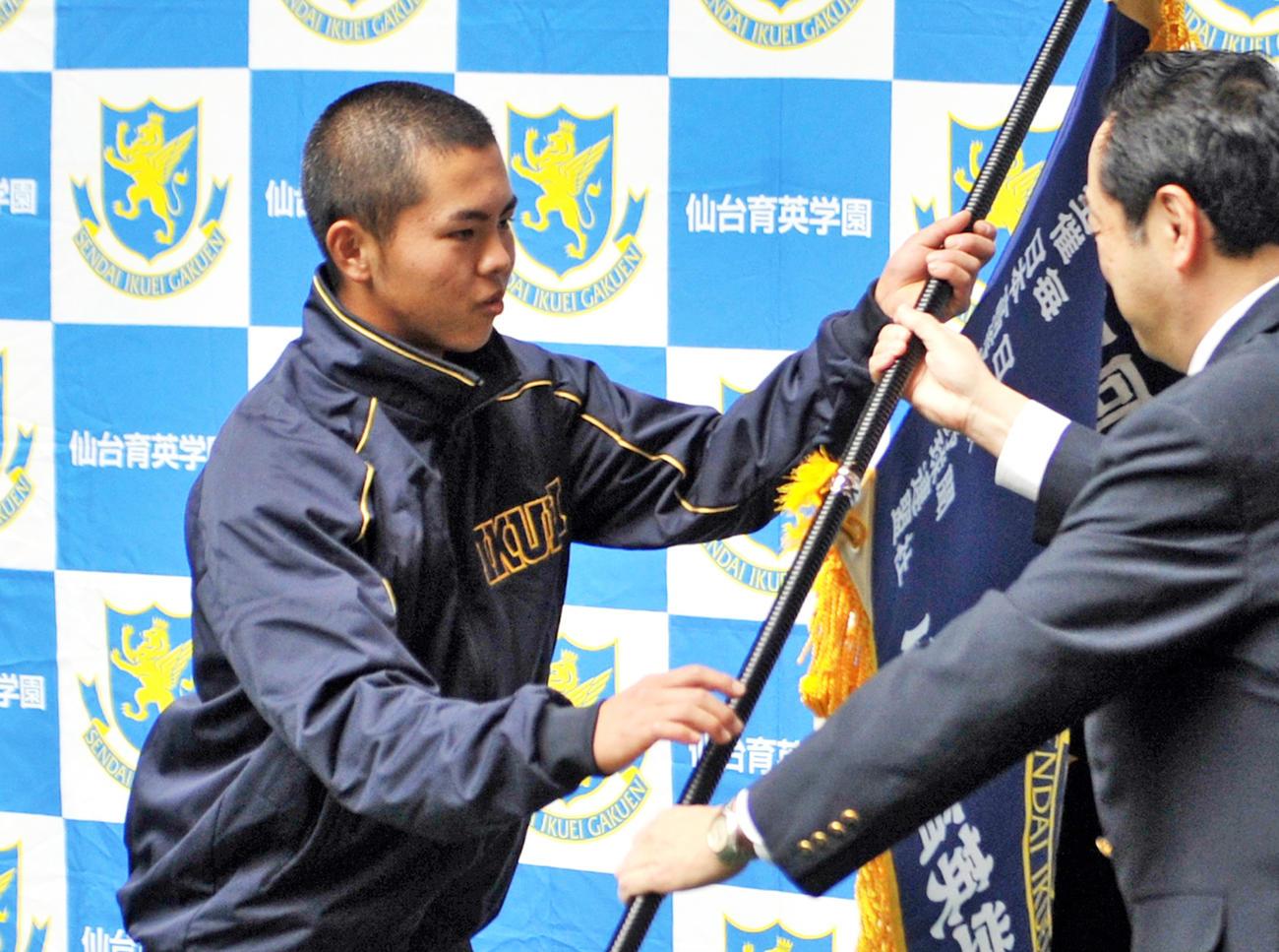 仙台育英の島貫主将(左)は加藤校長から選抜旗を受け取る(撮影・佐々木雄高)