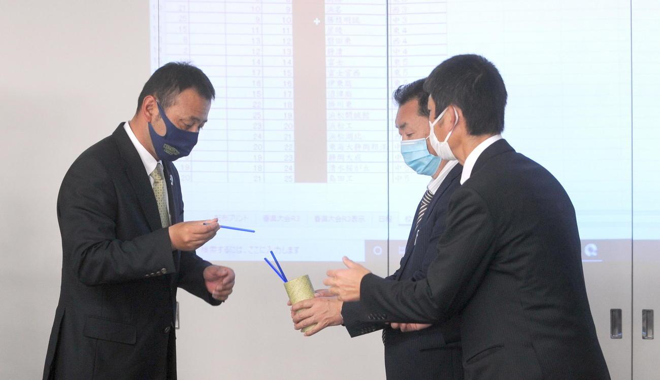 抽選箱からくじを引く三島南の稲木監督(左)
