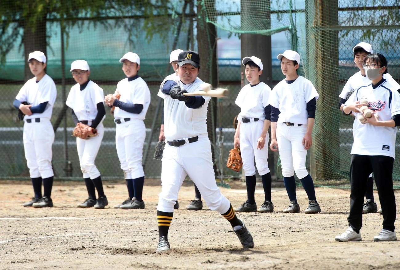 守備練習で打球を放つ仙台東・芳賀監督(中央)